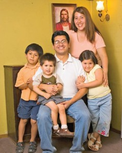 Mormon Family posing in front of painting of Jesus Christ.