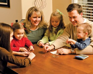 Mormon Family playing games around the kitchen table.
