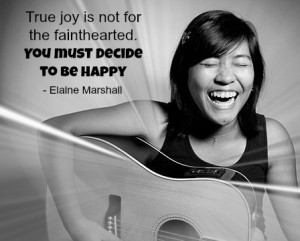 A girl playing her guitar and smiling very big with a quote about happiness from Elaine Marshall.
